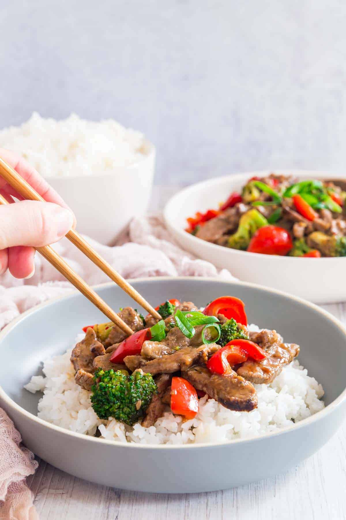 someone holding chopsticks to pick up stir fry beef and veggies over rice