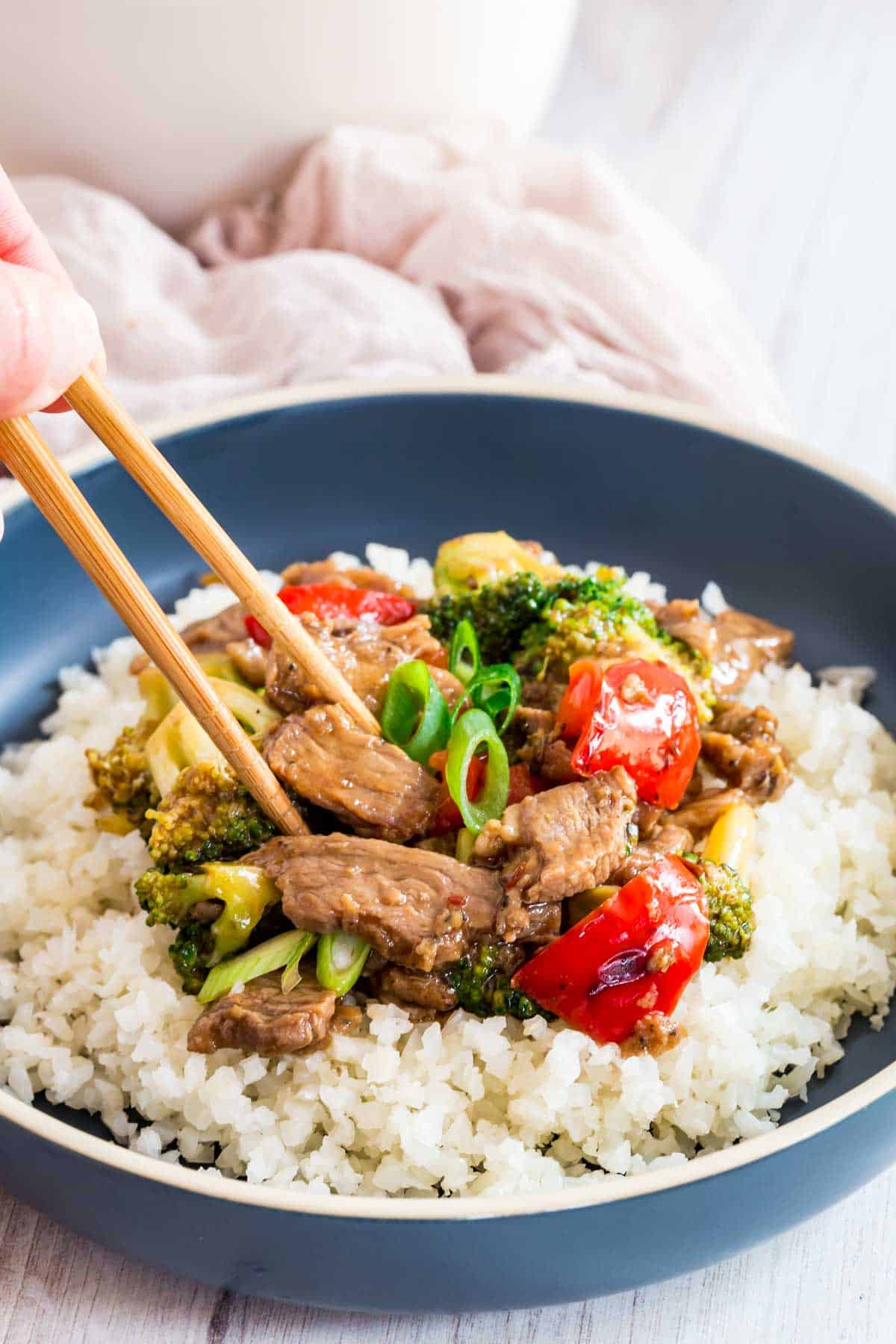 chopsticks picking up some hunan beef served over cauliflower rice in a blue bowl