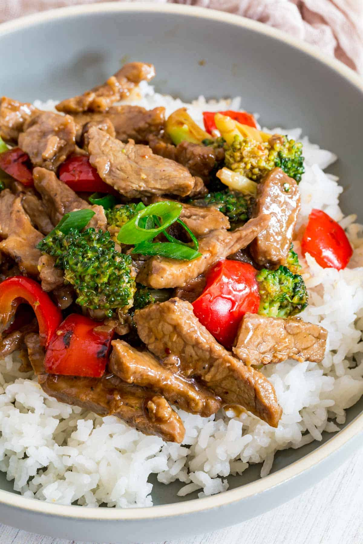 hunan beef stir fry with red peppers and broccoli over white rice in a light blue bowl