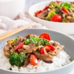 hunan beef with red peppers and broccoli on top of white rice in a light blue bowl