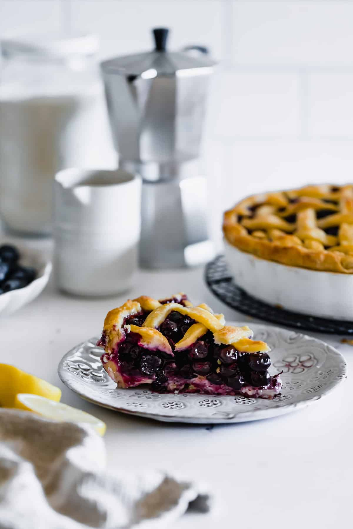 A Slice of Blueberry Pie on a Plate with the Full Pie in a Pan Behind It