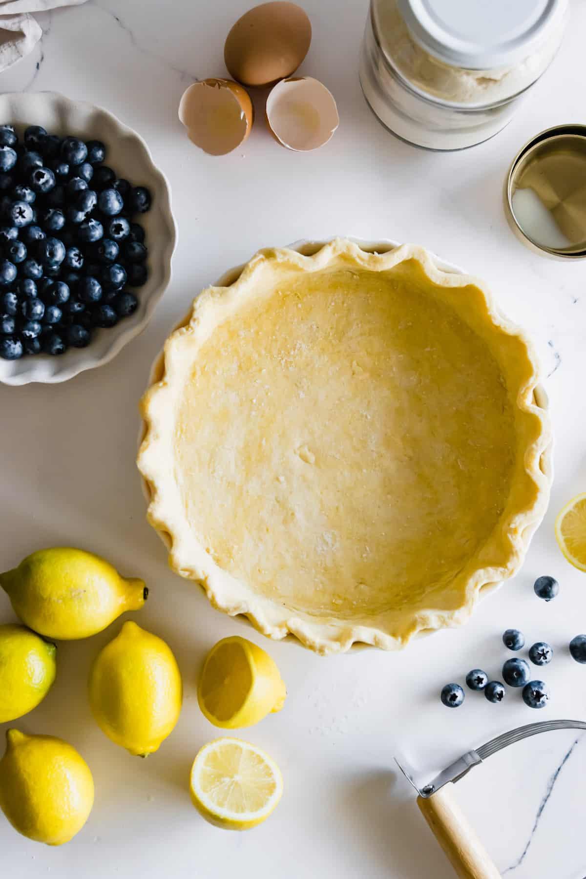 A Homemade Pie Crust, Fresh Lemons, Fresh Blueberries and Egg Shells on a Countertop