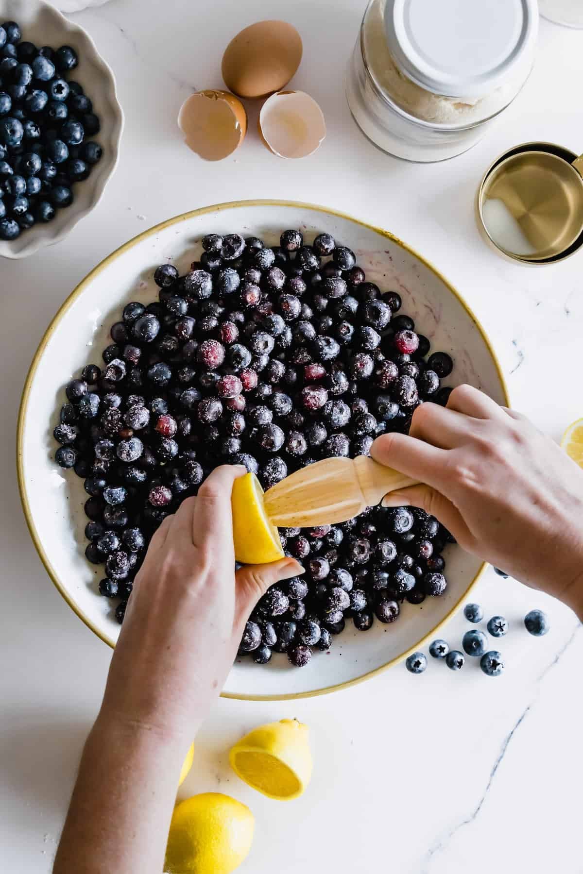 A Lemon Being Juiced Over a Bowl of Fresh Blueberries