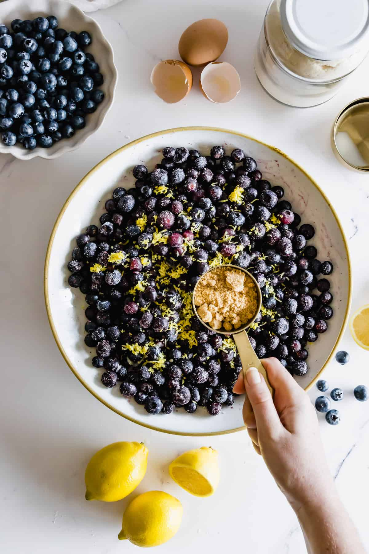 Brown Sugar Being Added to a Bowl of Blueberries, Lemon Juice and Lemon Zest