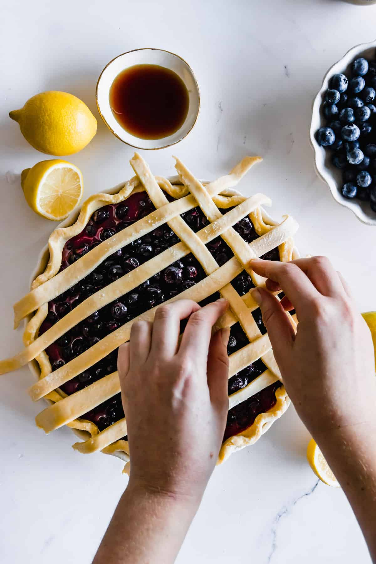Two Hands Assembling the Lattice Top to a Blueberry Pie