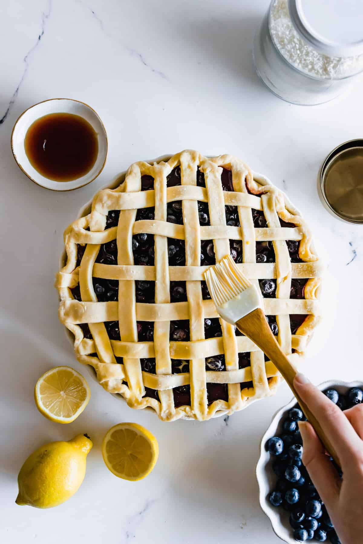 Eggwash Being Brushed Over a Blueberry Pie with a Pastry Brush