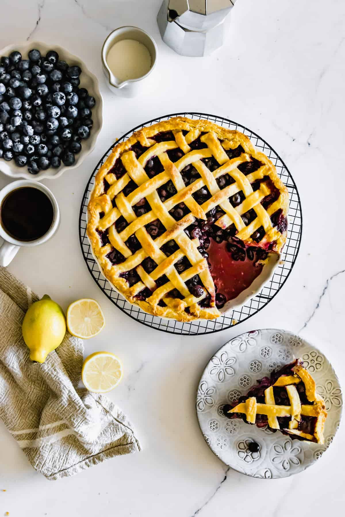 A Gluten-Free Blueberry Pie on a Metal Cooling Rack with One Piece on a Flowery Plate