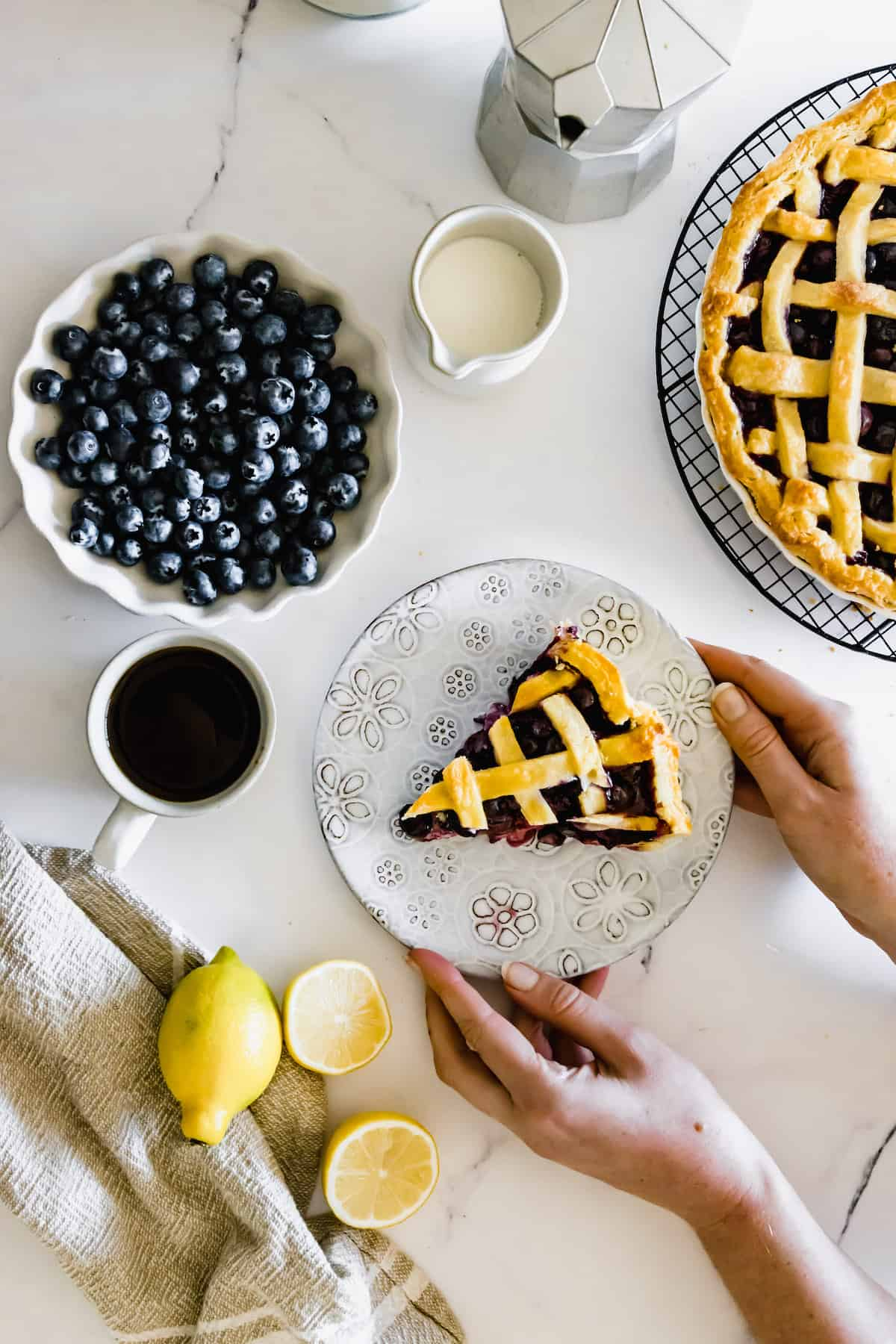 A Pair of Hands Grabbing a Plate of Pie Beside a Bowl of Fresh Blueberries