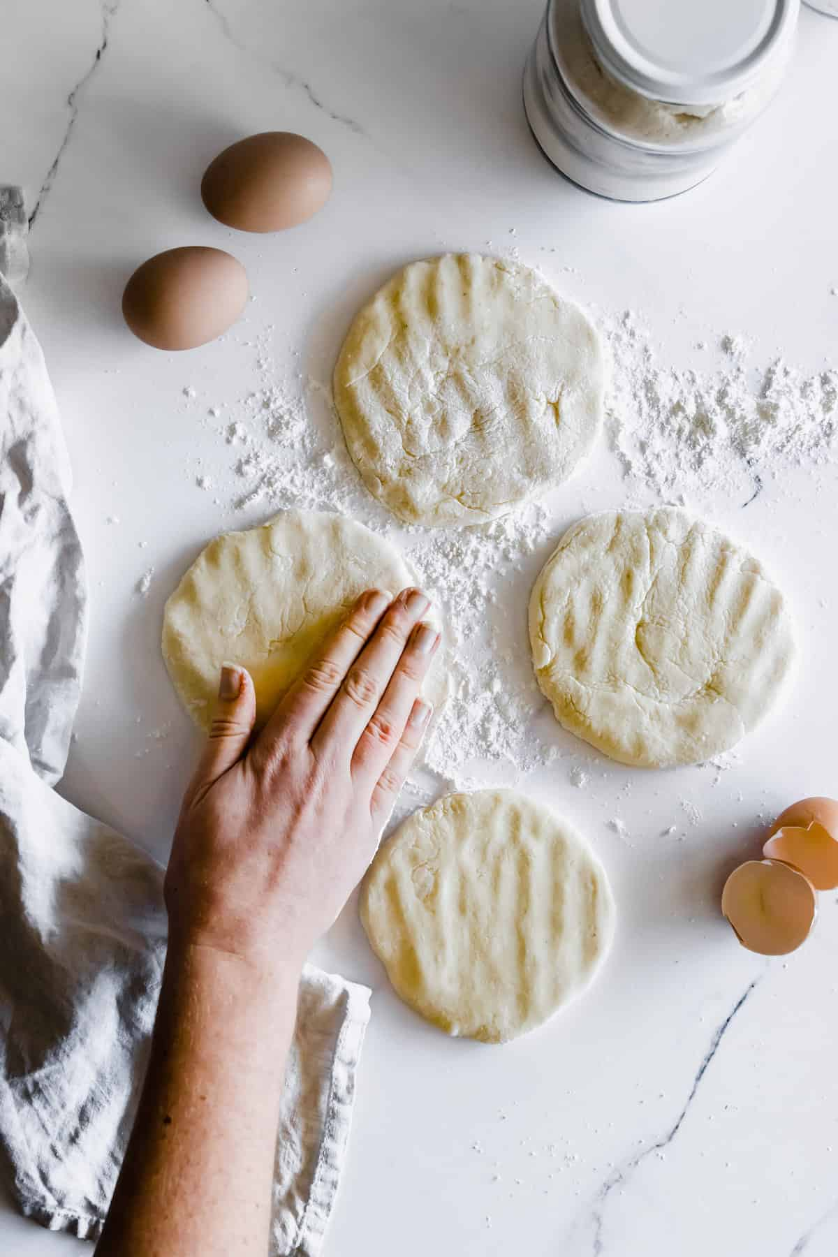 Four Discs of Gluten Free Pita Dough on a Marble Countertop with a Hand Pressing Down on One of Them