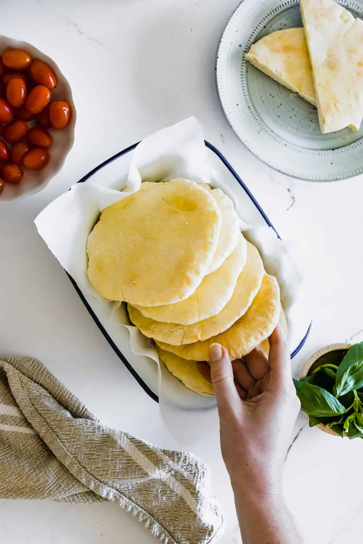 A Hand Grabbing a Piece of Pita Bread From a White Platter with a Blue Rim