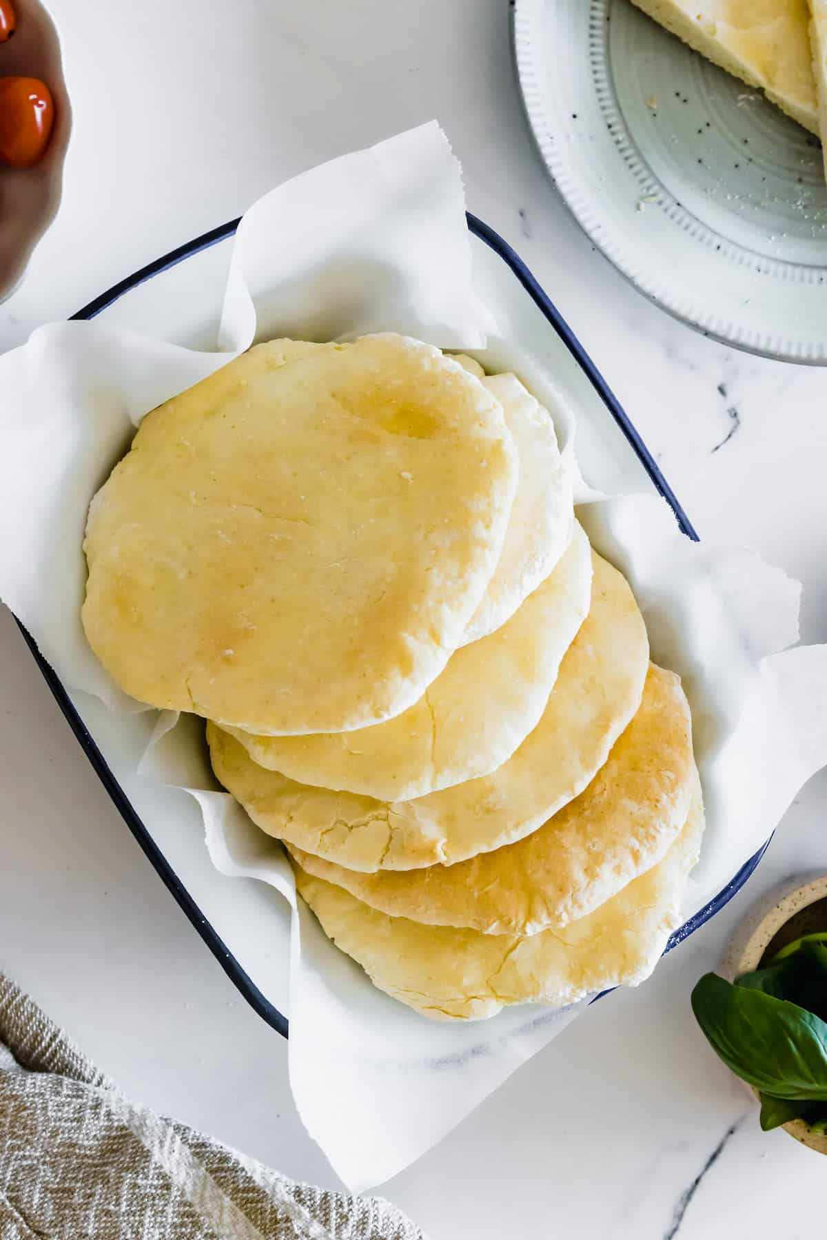 Six Pitas in a Serving Dish Lined with Parchment Paper