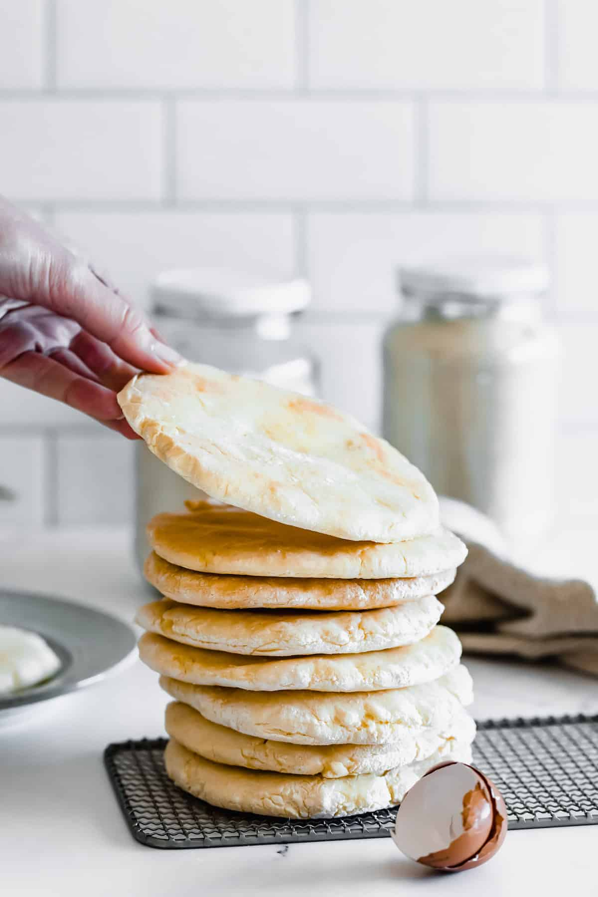 A Hand Grabbing a Piece of Pita Bread from the Top of the Stack
