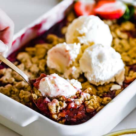 A Metal Spoon Being Dug Into a Fresh Pan of Strawberry Crumble