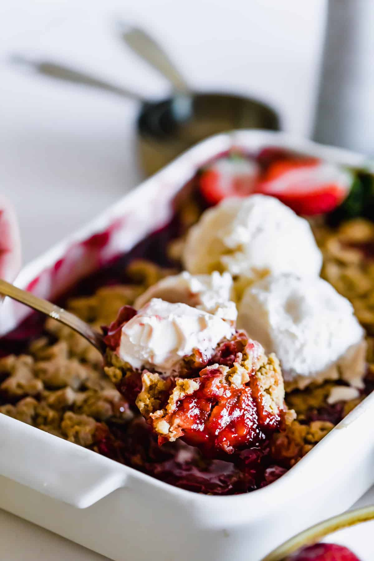 A Metal Spoon Holding a Scoop of Strawberry Crumble Over a Pan Full of the Dessert