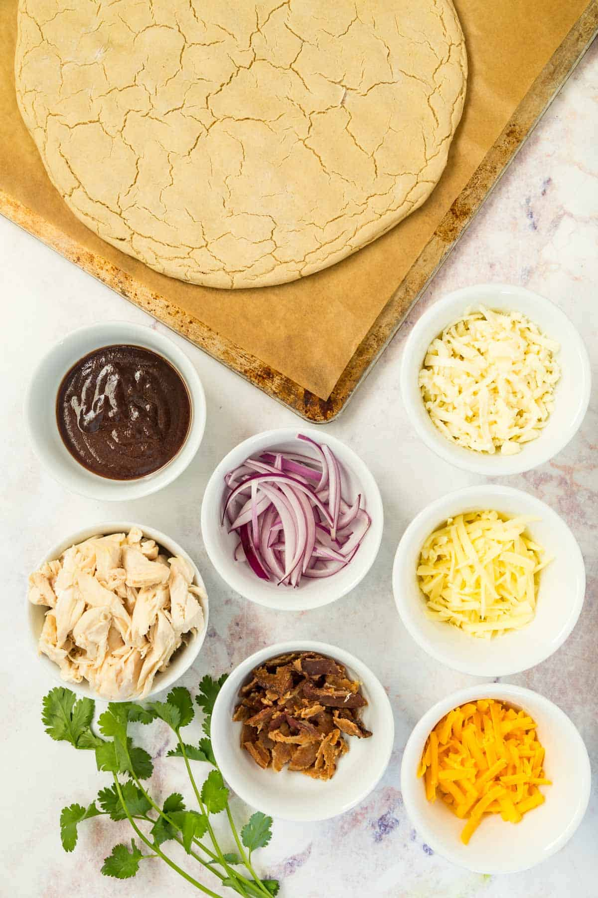 pizza crust plus bowls of barbecue sauce, chicken, three kinds of cheese, crumbled bacon, and sliced red onions, plus a bunch of cilantro on a marble tabletop