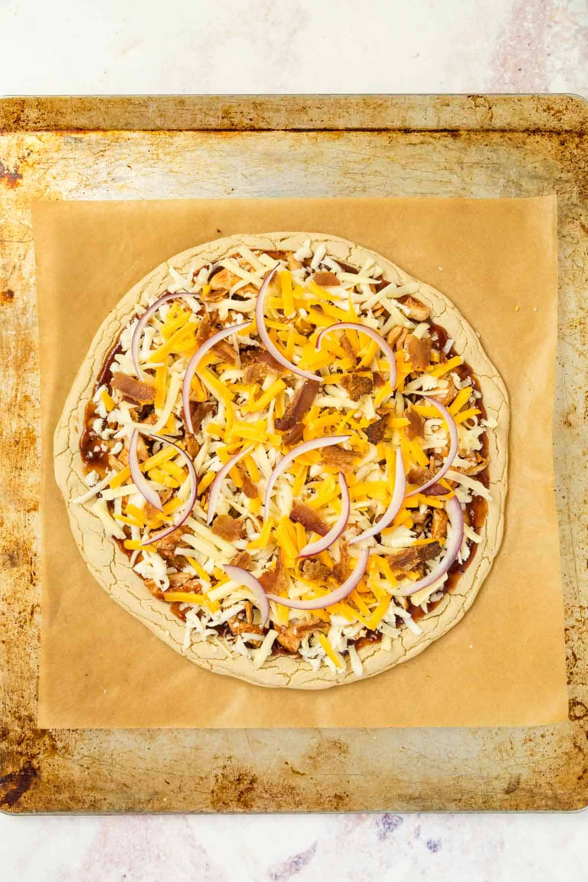unbaked barbecue chicken pizza on a parchment lined baking sheet