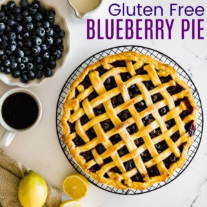 whole blueberry pie with a lattice top next to a bowl of blueberries and some lemons