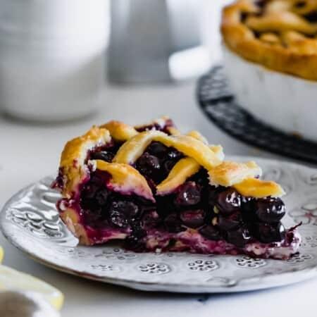 a slice of lattice-top blueberry pie on a decorative plate