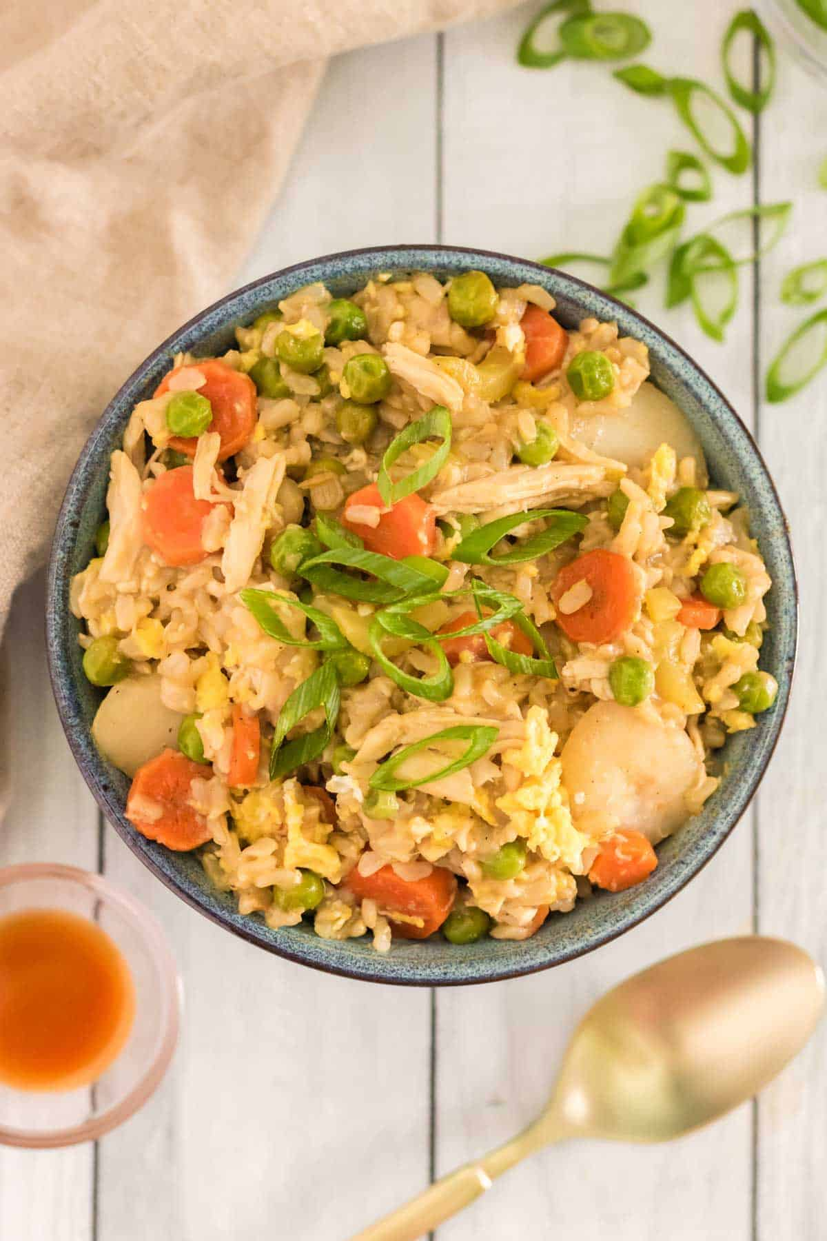 bowl of chicken fried rice with carrots, brown rice and shredded chicken