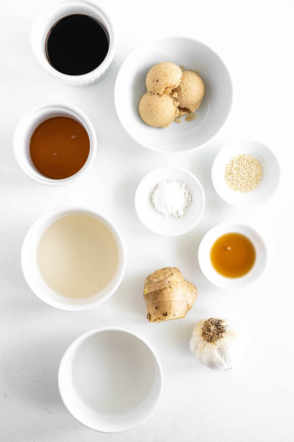 ingredients for gluten-free teriyaki sauce in small bowls, including soy sauce, brown sugar, honey and ginger