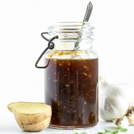 teriyaki sauce in a bottle next to a piece of fresh ginger and a bulb of garlic