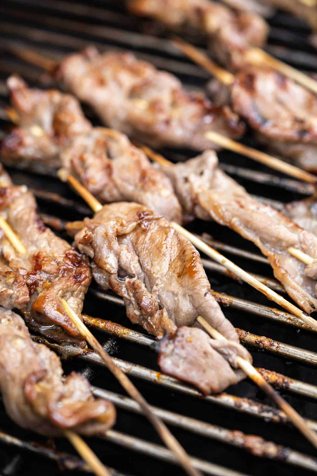 grilling skewers of steak on a gas grill