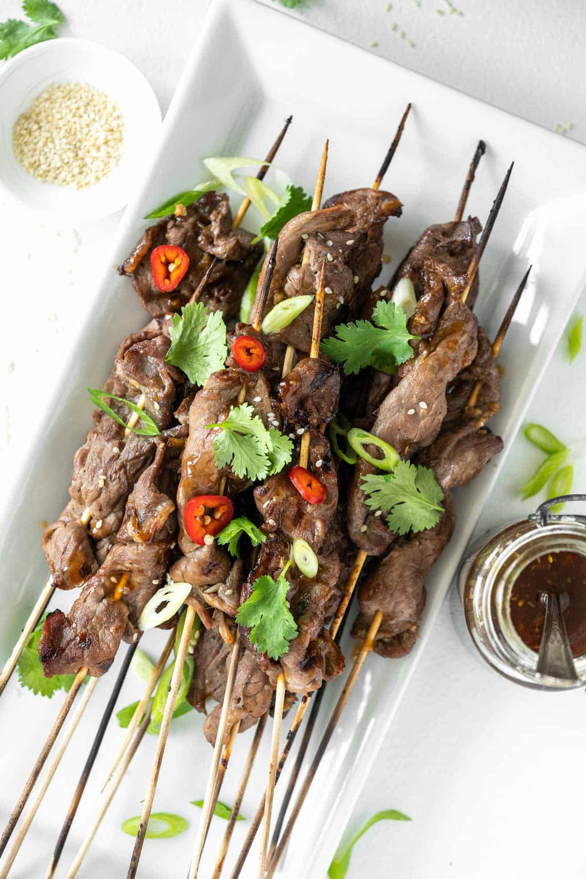overhead of a white platter with grilled steak skewers topped with peppers and herbs
