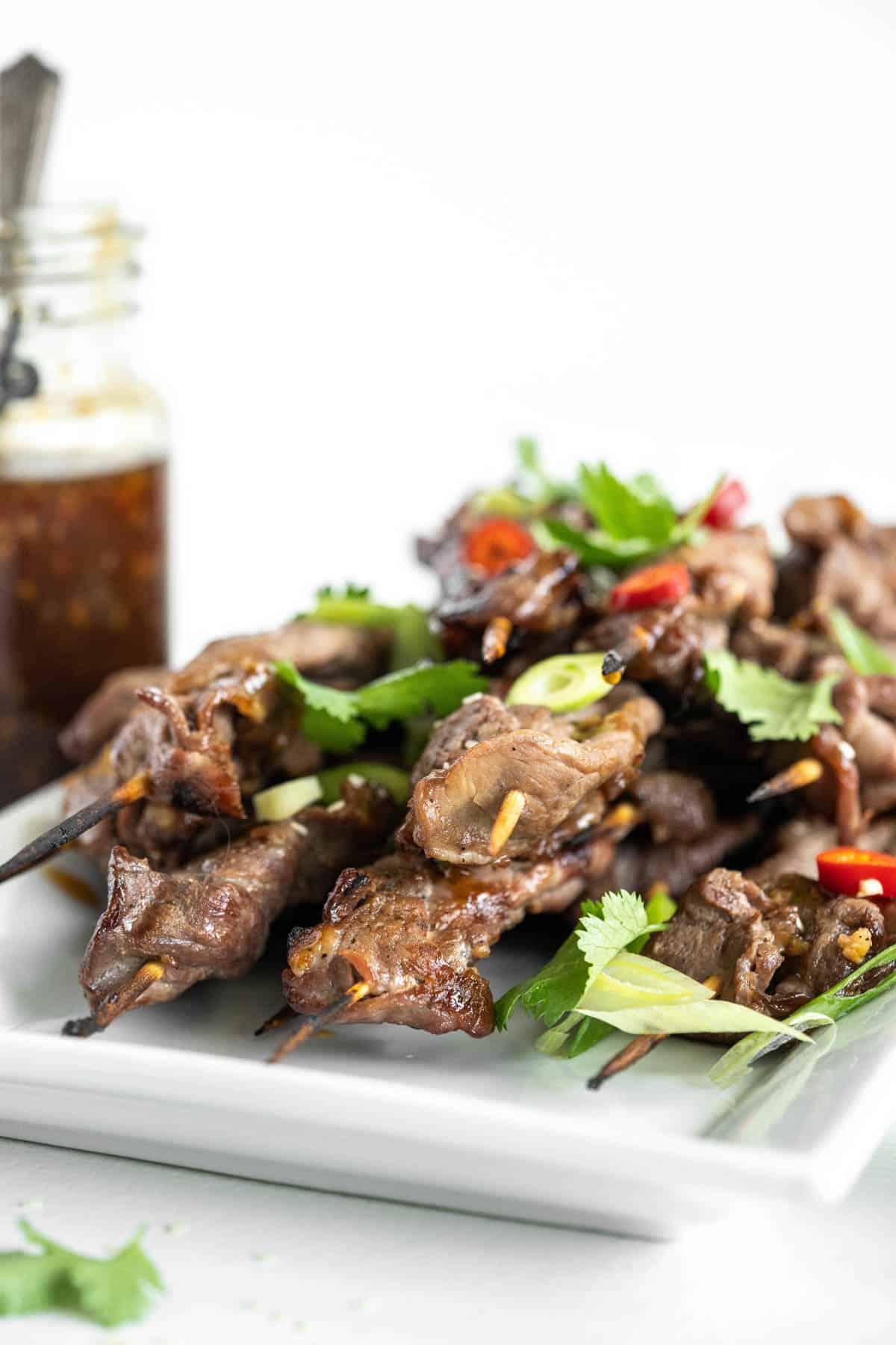 white platter of grilled steak skewers with teriyaki sauce