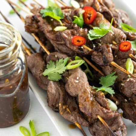 grilled teriyaki steak skewers on a platter with peppers and herbs on top