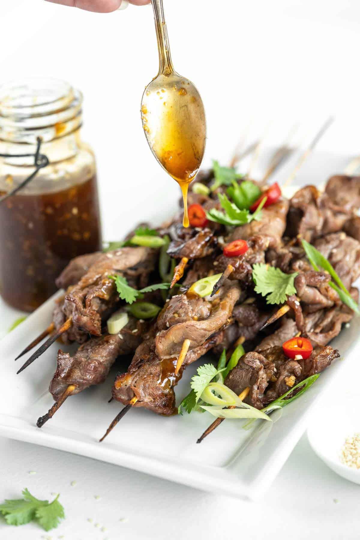 spoon drizzling teriyaki sauce over grilled steak skewers