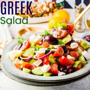 bowl of Greek salad with tomatoes, peppers, olives, cucumbers, onions, and feta and some being picked up with a spoon