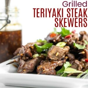 grilled steak skewers on a white platter garnished with cilantro and scallions