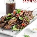 grilled steak skewers on a platter next to a bottle of teriyaki sauce and a bowl of sesame seeds