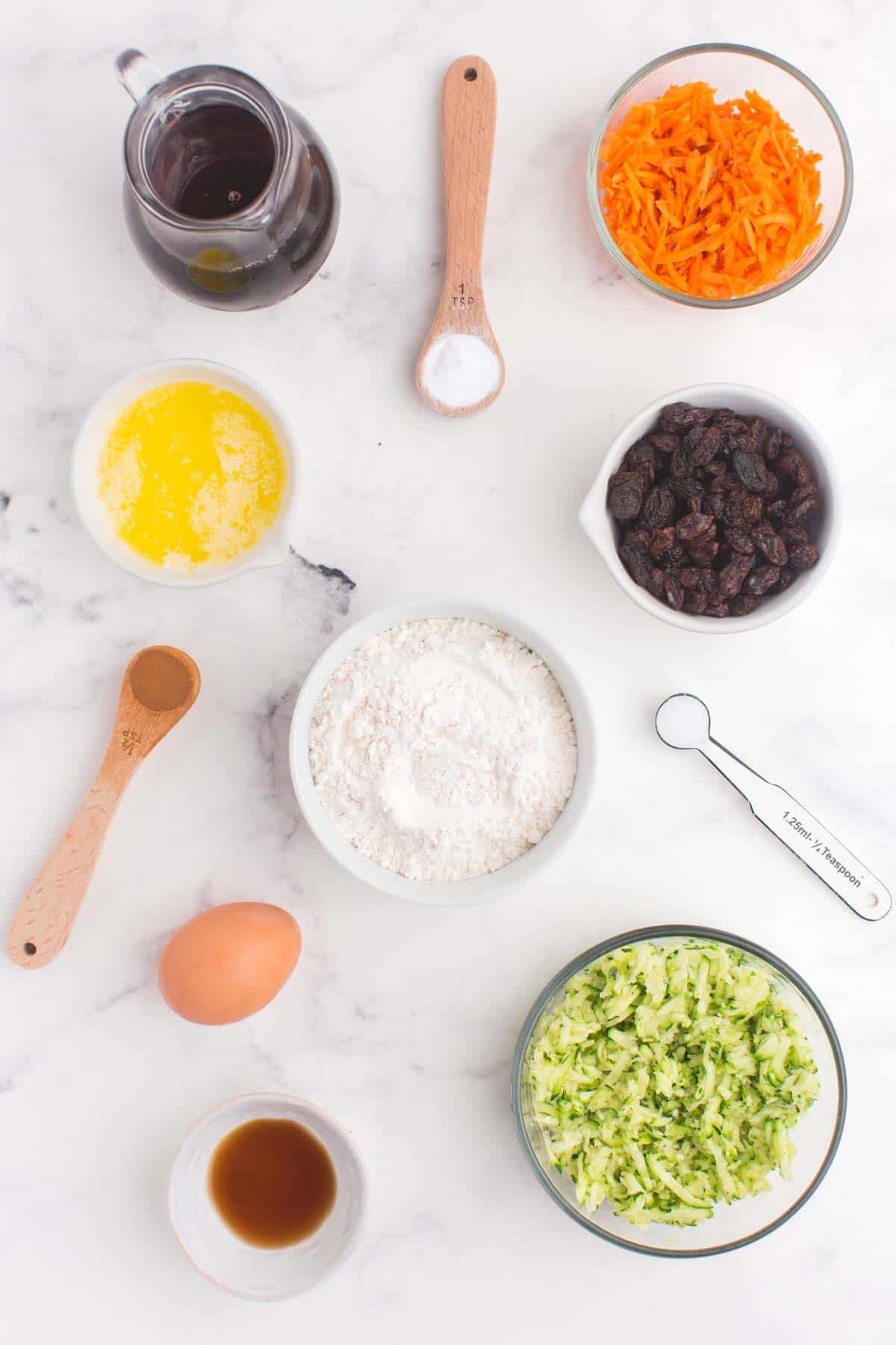 bowls of flour, shredded carrots and zucchini, vanilla extract, raisins, and melted butter, a pitcher of maple syrup, an egg, and spoons with cinnamon, salt, and baking soda on a marble tabletop