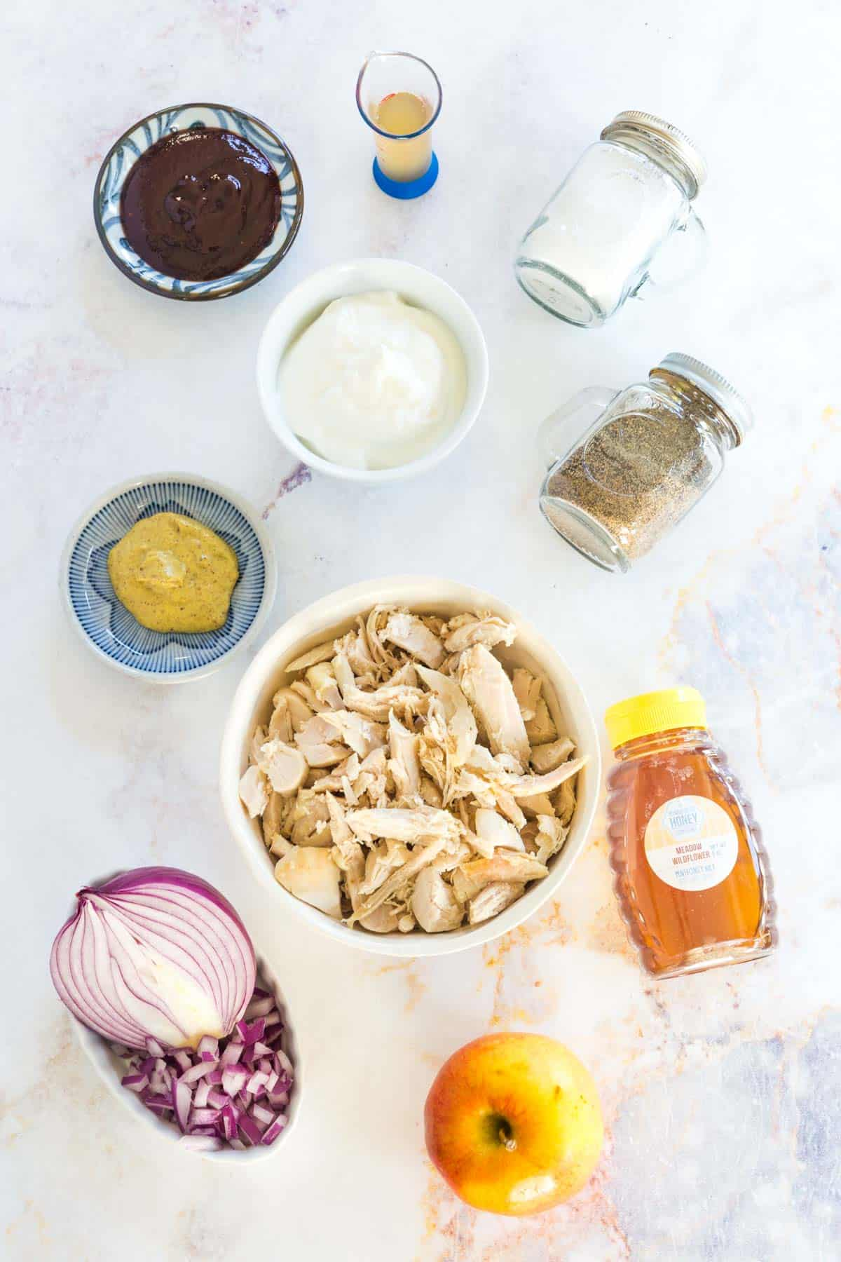 bowls of cooked chicken, Greek yogurt, mustard, barbecue sauce, apple cider vinegar, and red onion, an apple, a bottle of honey, and salt and pepper shakers