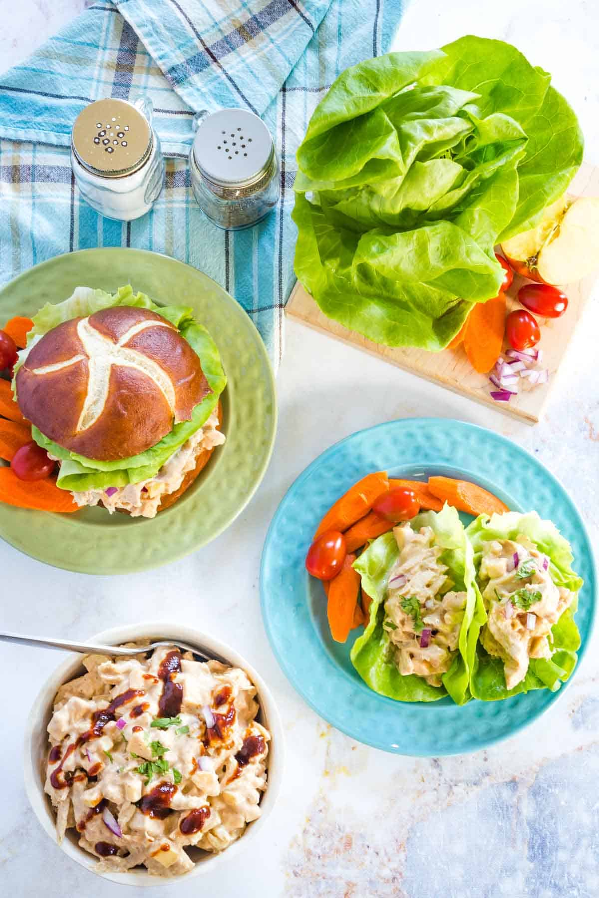 bbe chicken salad sandwich and lettuce wraps on plate with a bowl filled with more of the barbecue chicken salad, plus lettuce on a cutting board