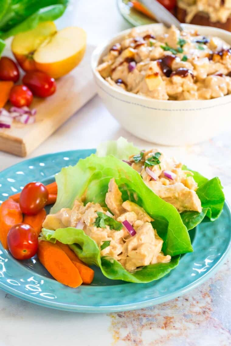 chicken salad lettuce wraps on a blue plate with carrots and tomatoes on the side