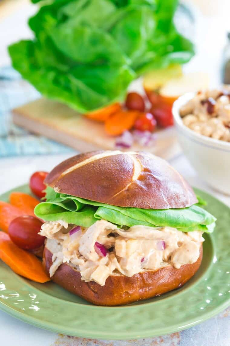 barbecue chicken salad sandwich on a roll with carrots and tomatoes on the side on a green plate