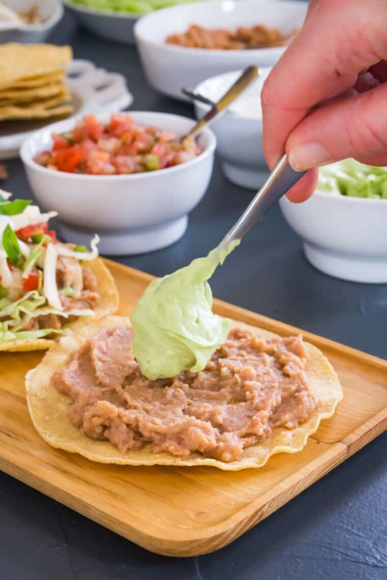 refried beans on a tostada shell and a spoon dolloping guacamole on top