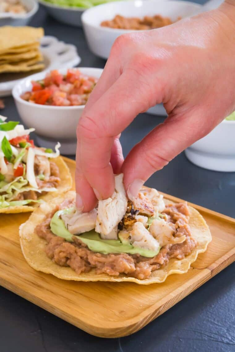 hand placing chicken on top of the tostada