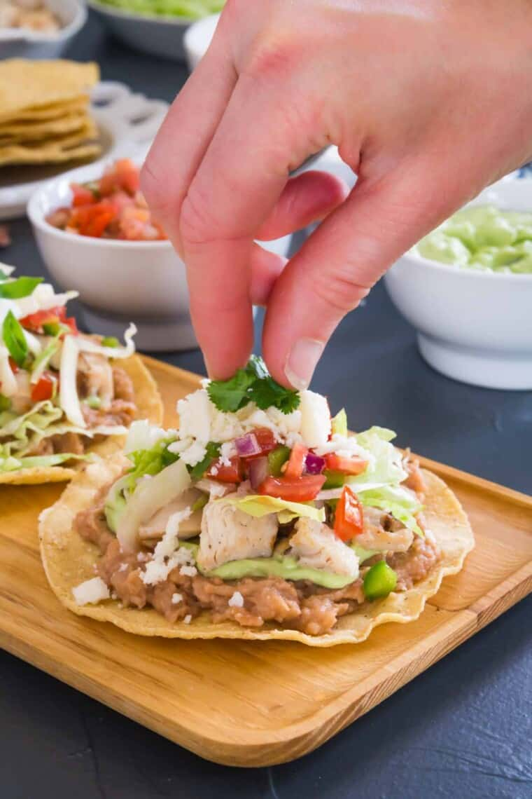 adding the cilantro garnish to the top of the finished chicken tostada