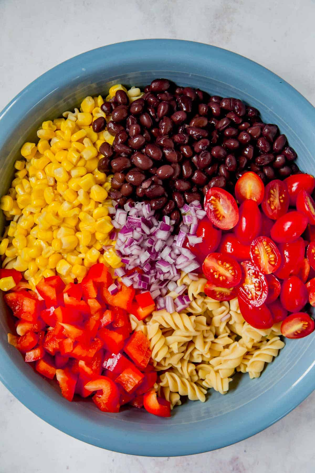 bowl of cooked pasta topped with red pepper, black beans, corn, halved grape tomatoes, and minced red onion