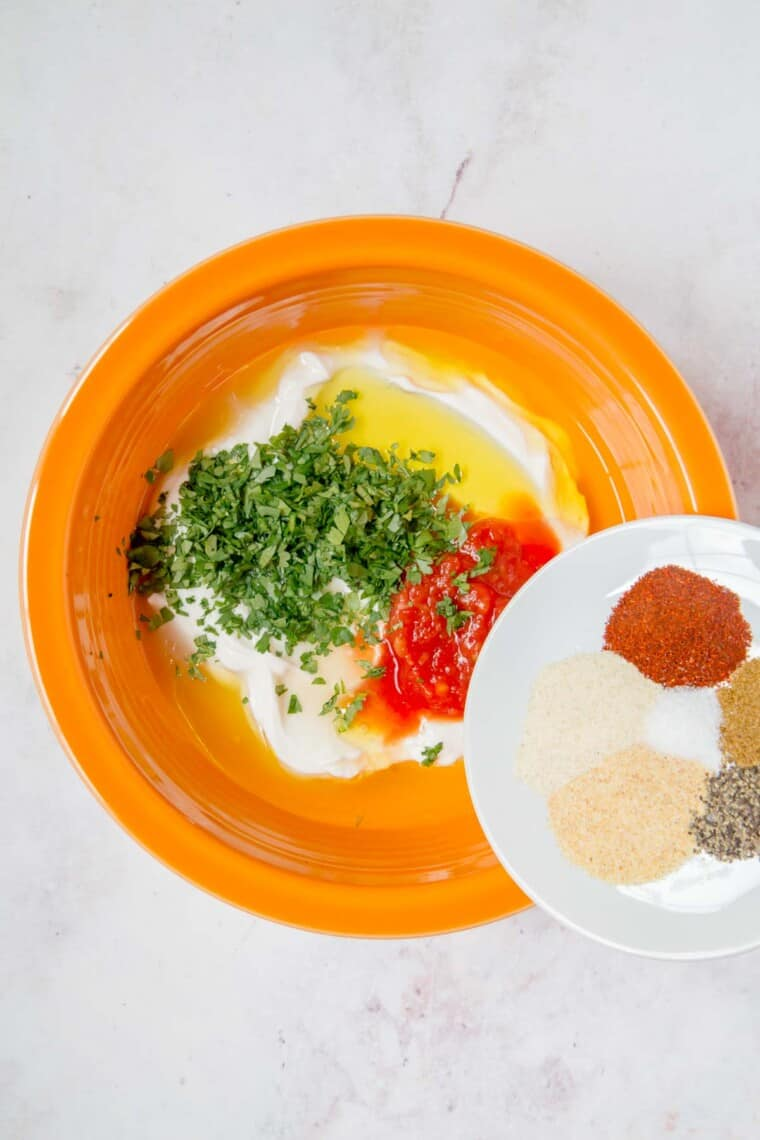 southwestern dressing ingredients in an orange bowl with the spiced being poured in from a white plate