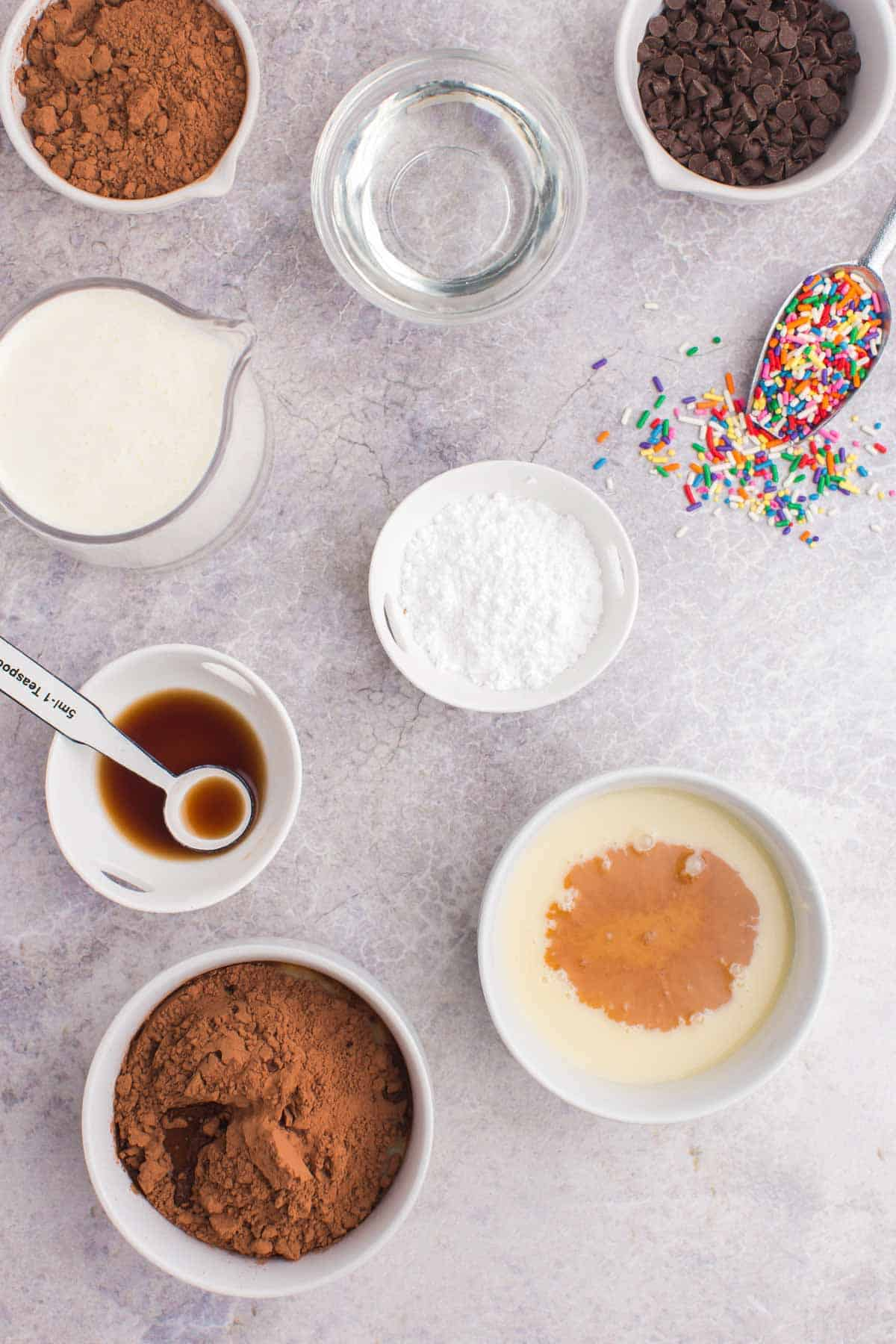 cocoa powder added to one bowl of sweetened condensed milk and vanilla extract added to another with all of the remaining ingredients still on the table