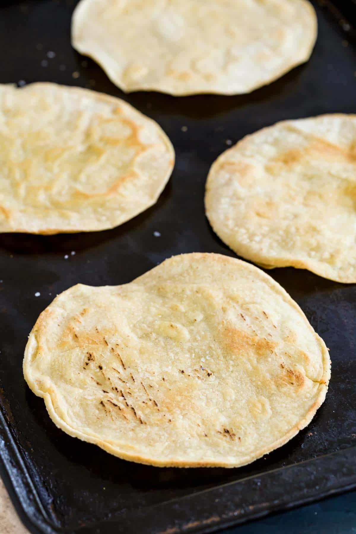 four baked tostada shells on a baking pan