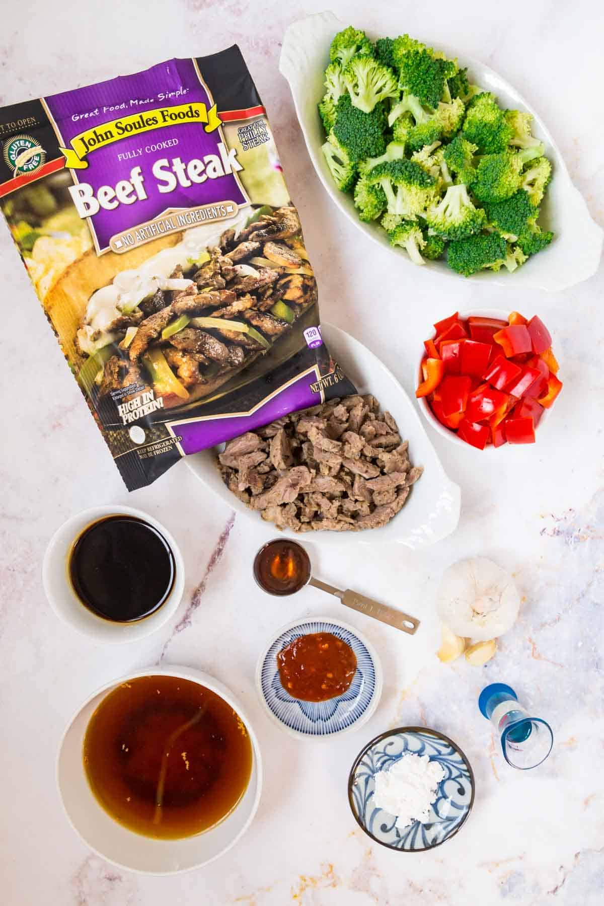 a package of John Soules Foods beef steak plus bowls of beef broth, soy sauce, chili paste, cornstarch, honey, oil, broccoli florets, and chopped red pepper and some garlic cloves