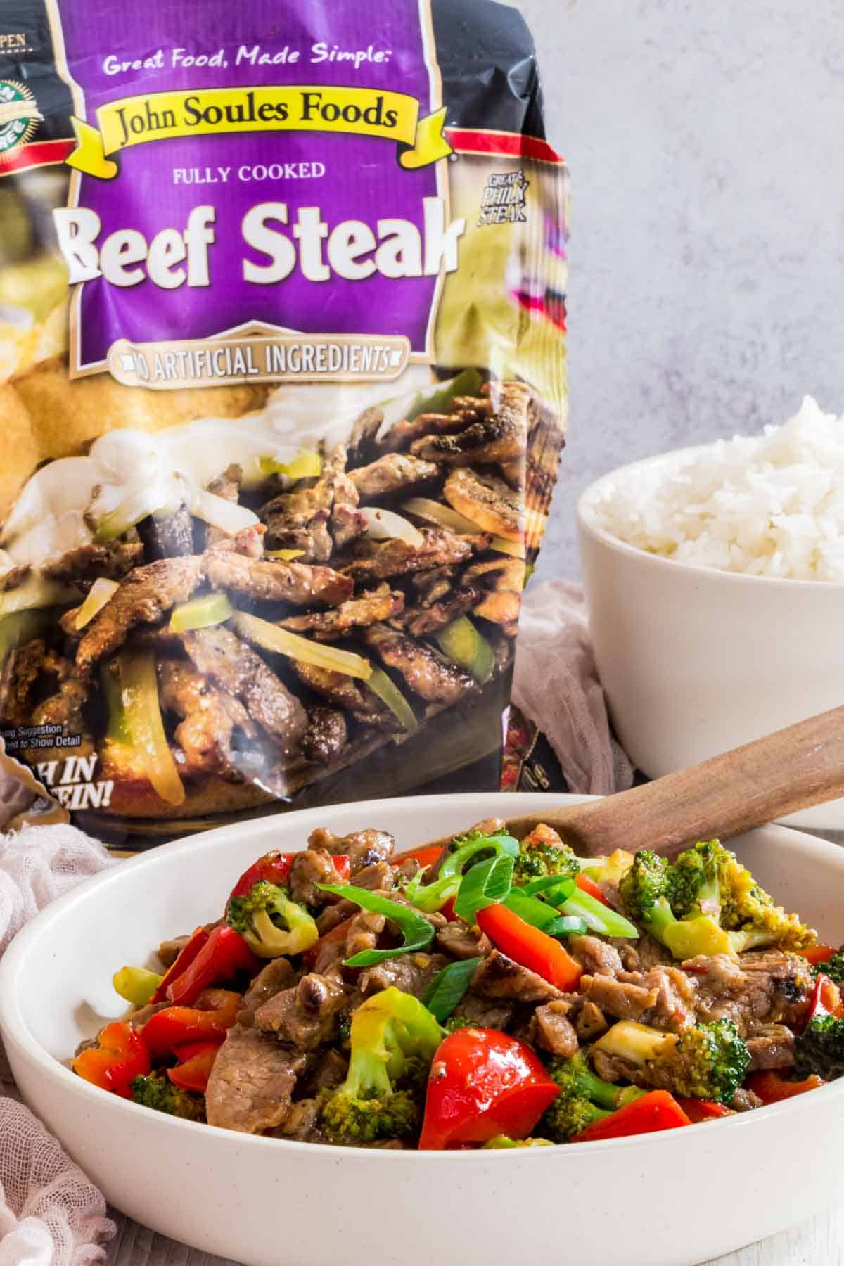 hunan beef in a serving bowl in front of a package of John Soules Foods Fully Cooked Beef Steak