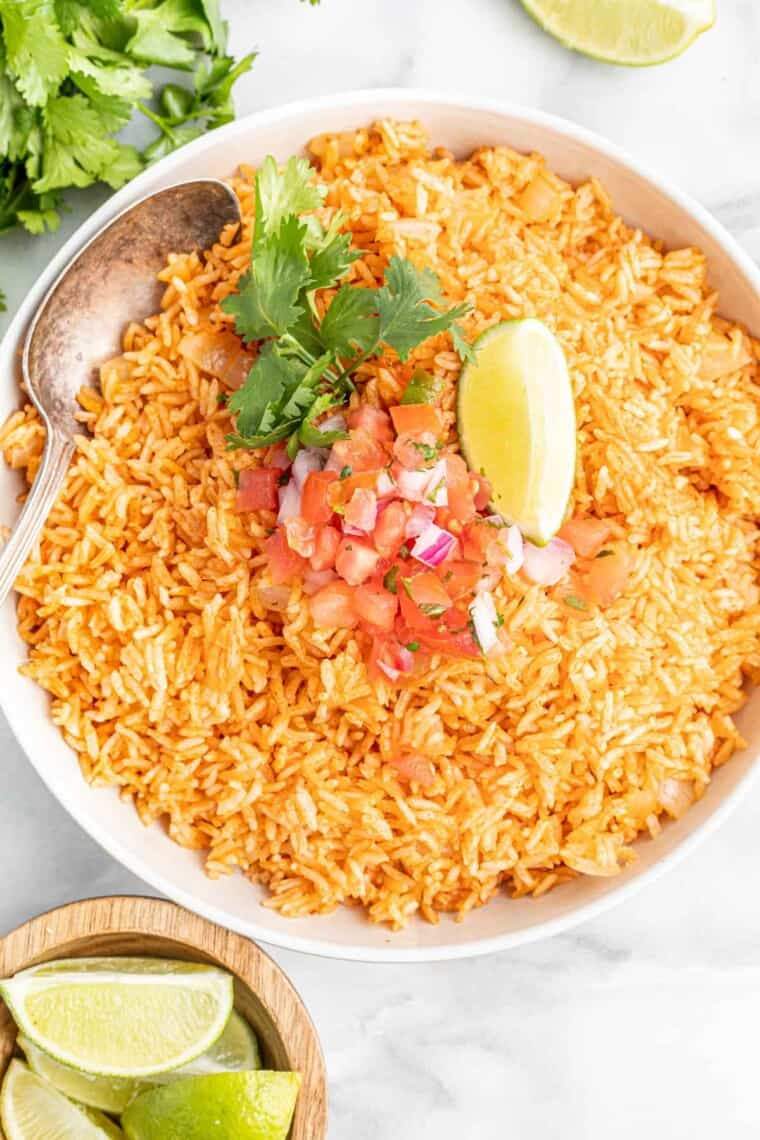 serving bowl of Mexican rice garnished with chopped tomatoes and onions, cilantro, and a lime wedge
