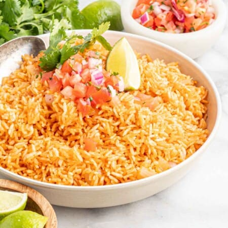 serving bowl of spanish rice with a bunch of cilantro and bowls of pico de gallo and lime wedges next to it