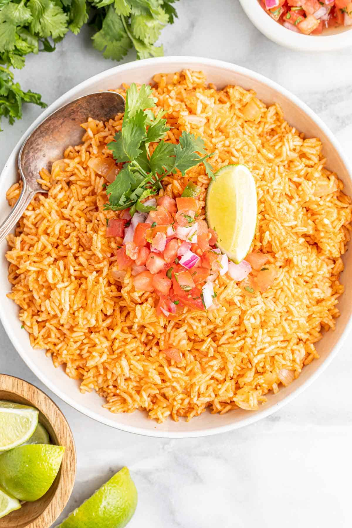 white bowl of spanish rice topped with chopped tomatoes and onions surrounded by bowls of salsa and limes